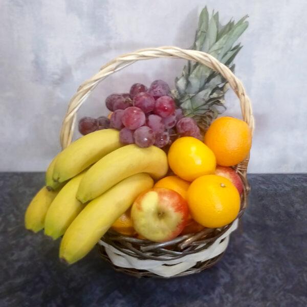 Бананы, апельсины и виноград в корзине